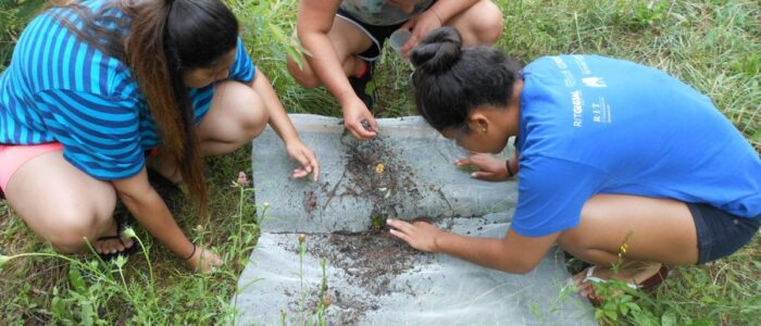 Youth inspecting dirt.