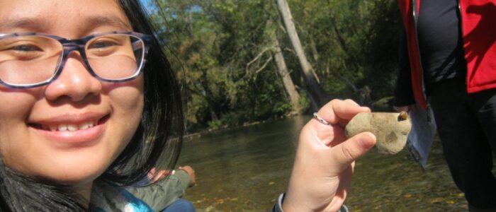 Youth holding rock with slug on it.
